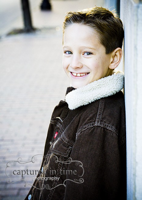 boy smiling brown coat