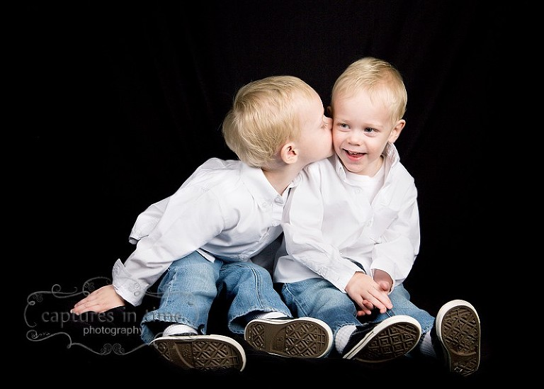 twin blonde boys on black backdrop