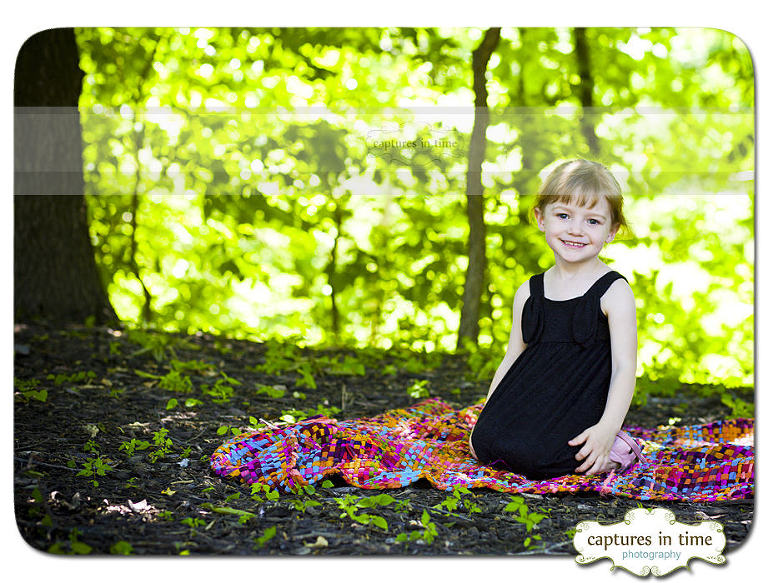 girl under tree on colorful blanket