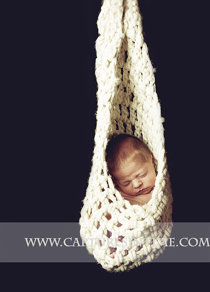 Kansas City Newborn Photographer photographs baby in knit slng