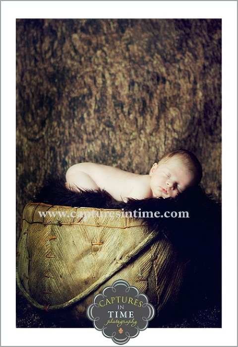 baby in dark brown rug and wooden basket on tummy