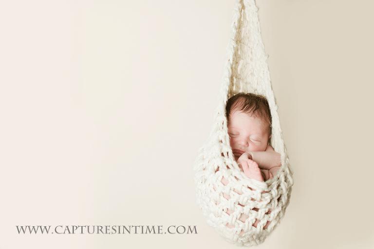 newborn hanging in hammock on cream