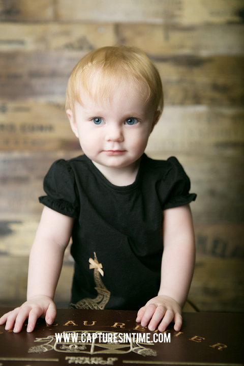 one year old girl black top standing in from of wood backdrop blue springs