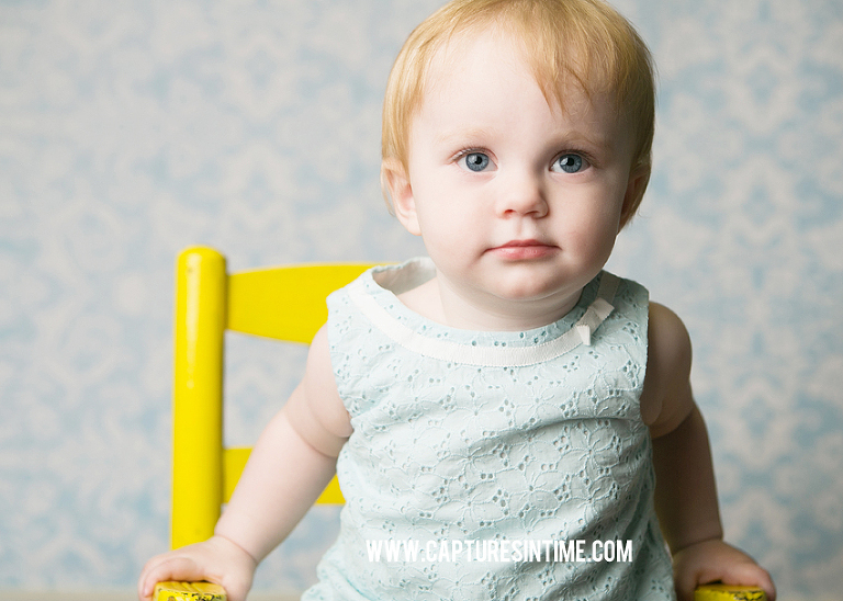 one year old girl blue top sitting in blue chair in front of blue backdrop blue springs
