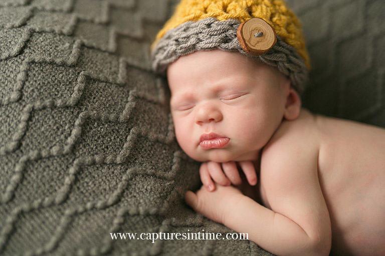 newborn photographer newborn baby boy with yellow and cream hat full lips and hand under his chin