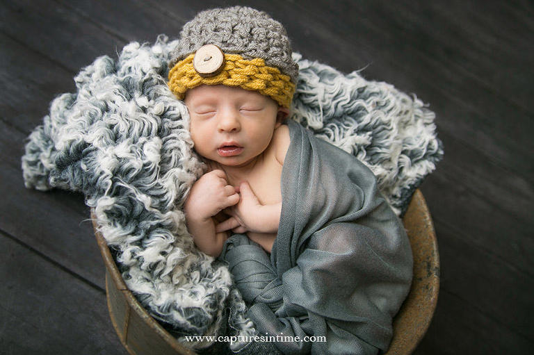 blonde newborn portrait on grey fur with grey and yellow hat