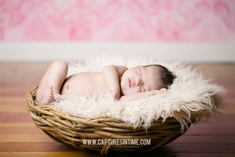baby sleeping with pink backdrop