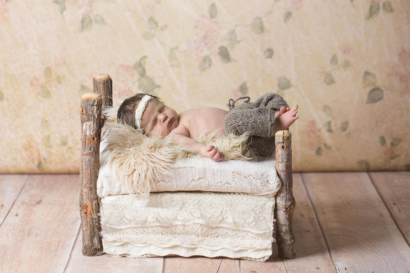 newborn girl in birch bed floral backdrop