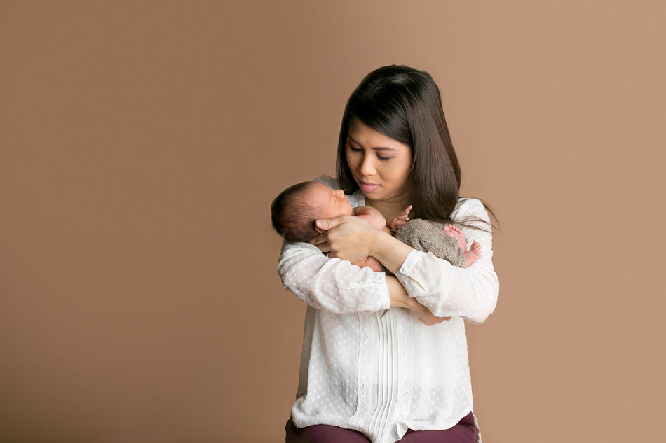 mom with cream blouse on holding new baby boy