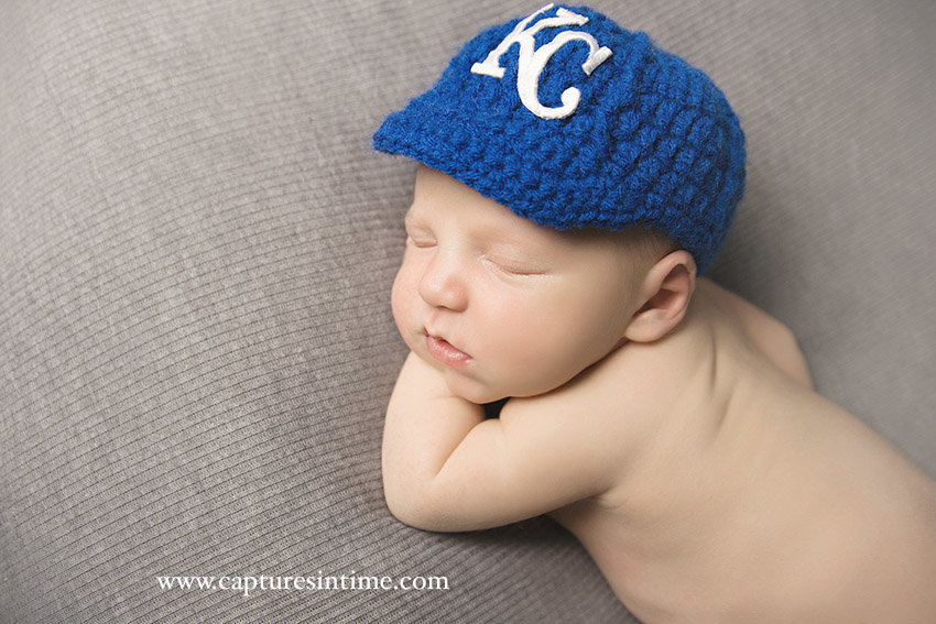 Newborn Baby Boy Photos kansas city royals newborn hat lying on grey fabric