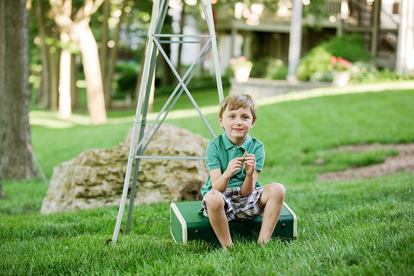 Kansas City Photographer boy in green shirt sitting next to windmill