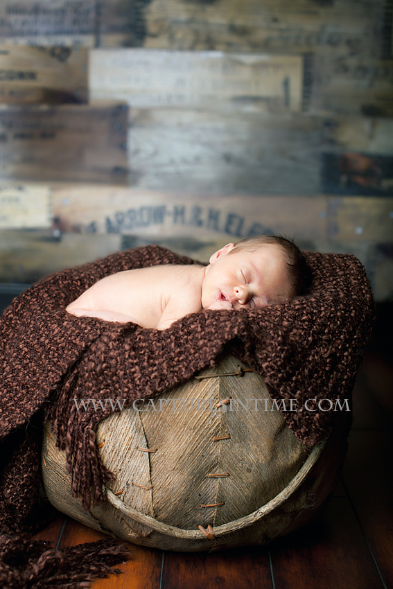 newborn on a brown blanket