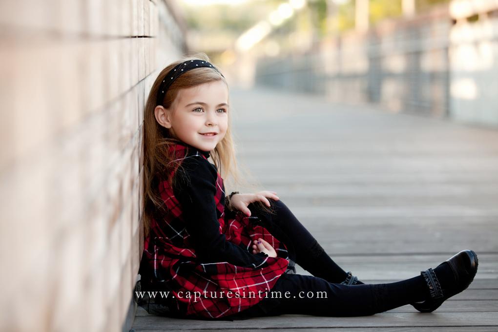 rivermarket girl in plaid dress sitting