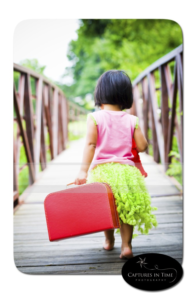 Railroad Park Blue Springs toddler with suitcase on bridge