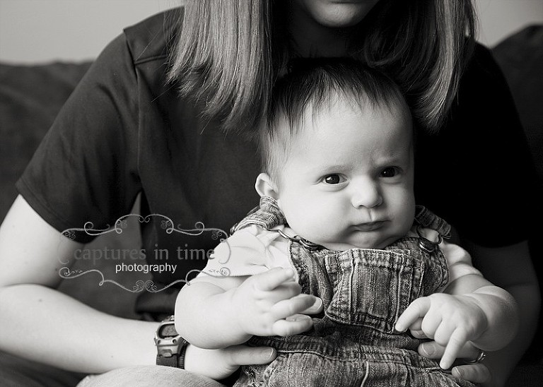 baby in overalls on mom's lap