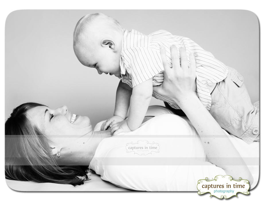 mom lying down holding baby