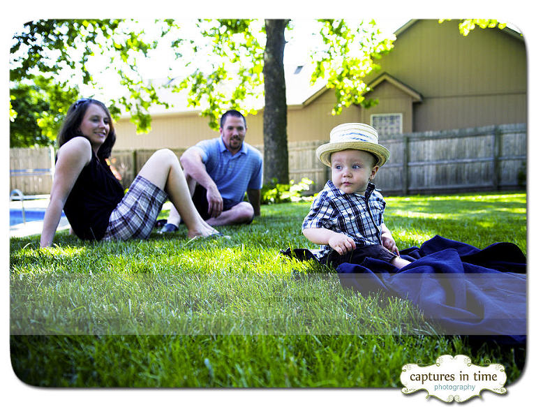 toddler with hat on sitting outside with family