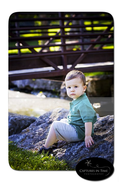 Kansas City Child Photographer boy sitting on a rock by a bridge