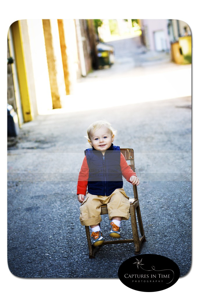 boy in vest sitting in an alley Kansas City