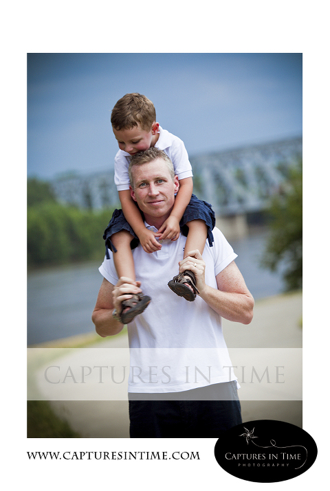 toddler boy on dad's shoulders with bridge in background River Market