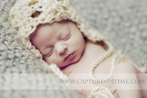 Kansas City Newborn Photographer photographs baby with cream knit hat