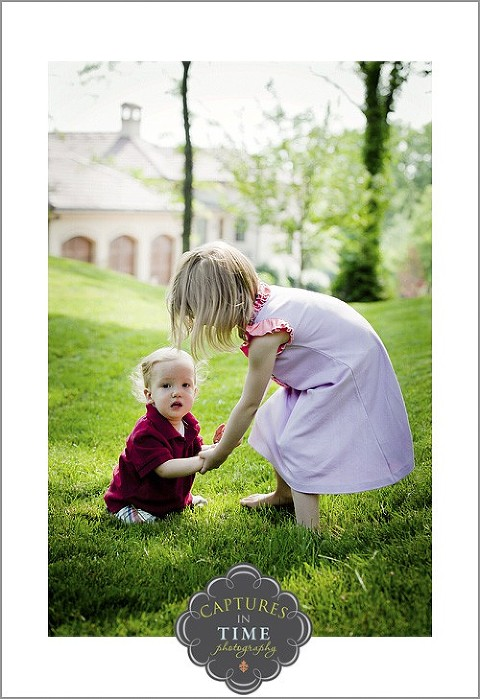 North Kansas City Child Photographer boy crawling in grass with sister's help