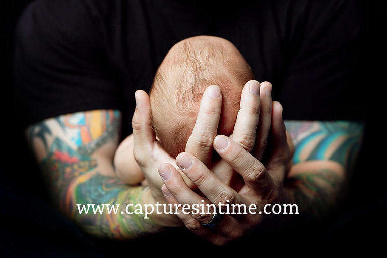 dad tattoos holding baby's head