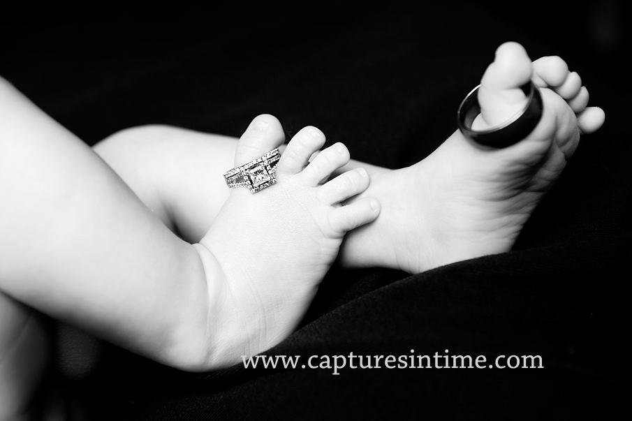black and white baby feet with wedding rings