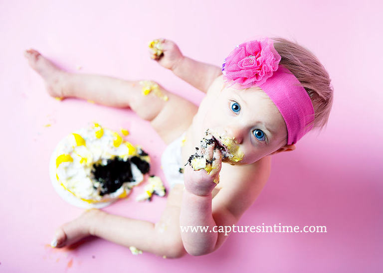 baby on hot pink eating chocolate cake