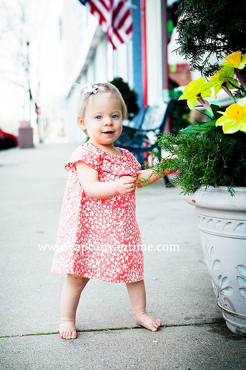 baby girl in orange dress outdoors by flowers