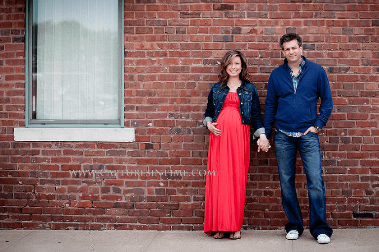 kansas city maternity session mom in red dress holding hands with dad