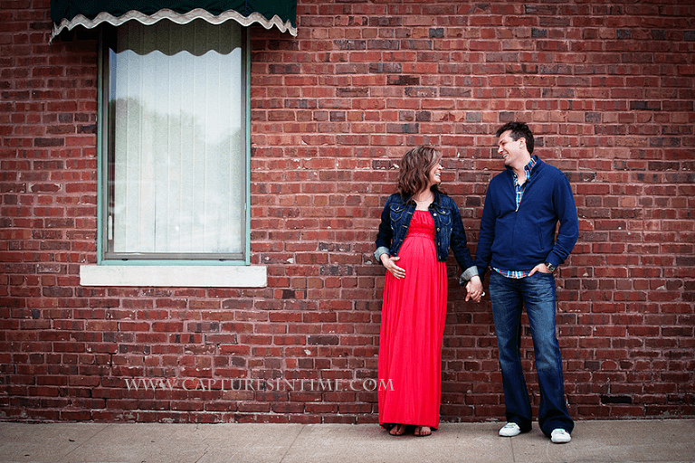 kansas city maternity session mom in red dress holding hands with dad looking at him