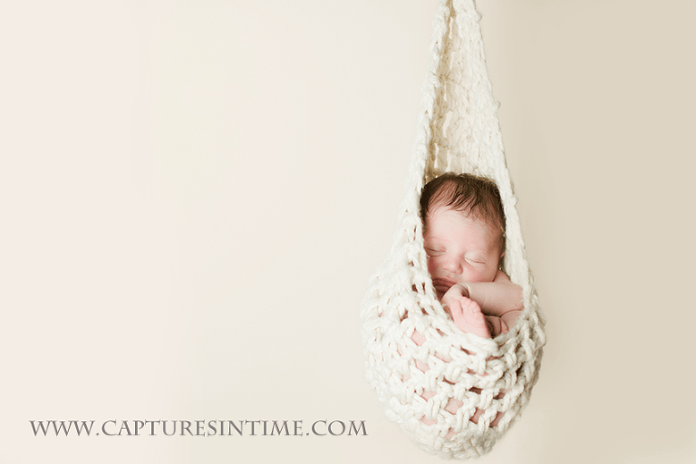 newborn hanging in hammock on cream