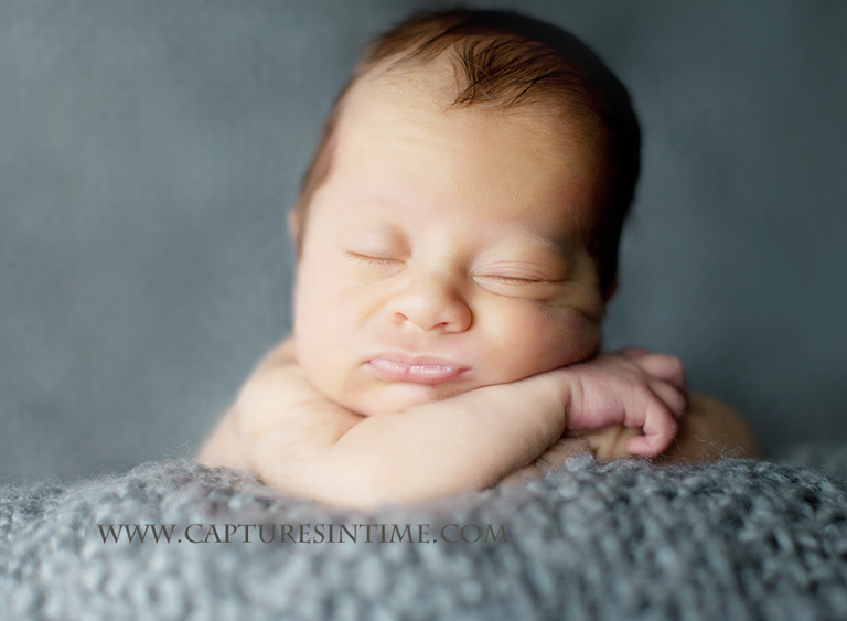 newborn photos on a grey blanket with funny face