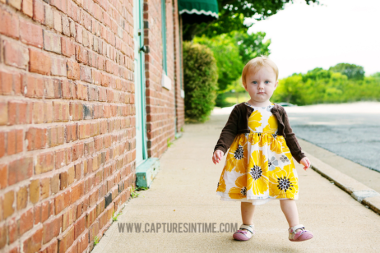 one year old girl floral dress walking next to brick building blue springs