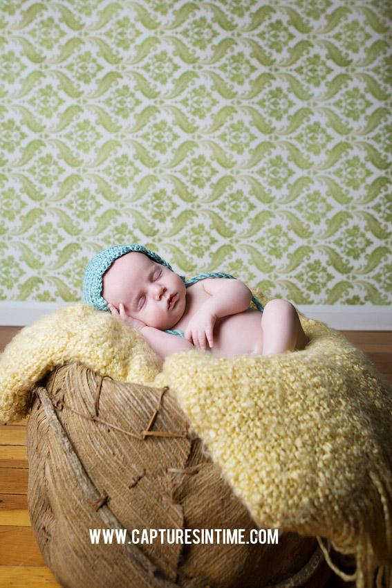 newborn on green damask backrop