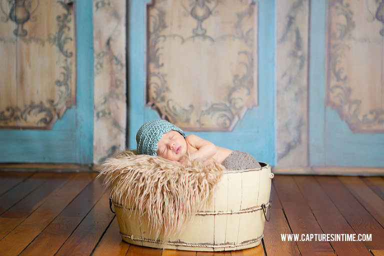 Grain Valley Newborn Photography newborn baby in front of armoire backdrop with teal hat on