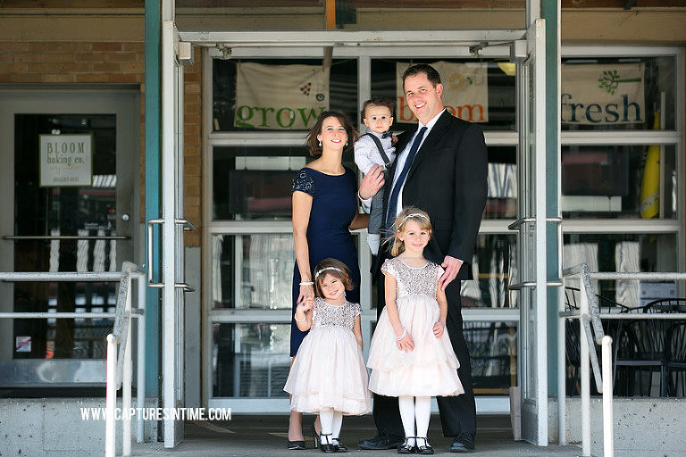 KC River Market Family Photography family dressed up in fancy clothing in front of bakery in Kansas City
