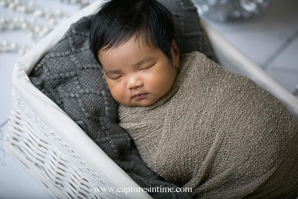 kansas city newborn photographer Mia newborn baby dark hair in white basket close up