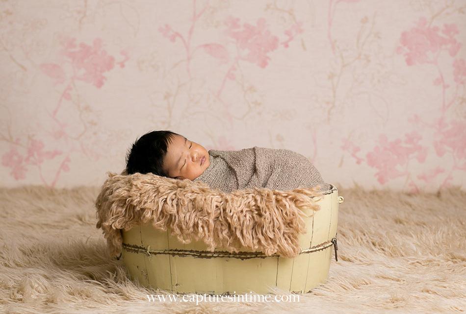 kansas city newborn photographer Mia newborn baby dark hair swaddled and sleeping with pink vine vintage backdrop