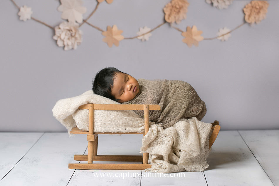 kansas city newborn photographer Mia newborn baby dark hair on vintage doll sleigh