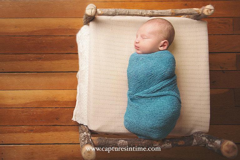 Newborn Baby Boy Photos newborn sleeping on rustic bed on old wood floor