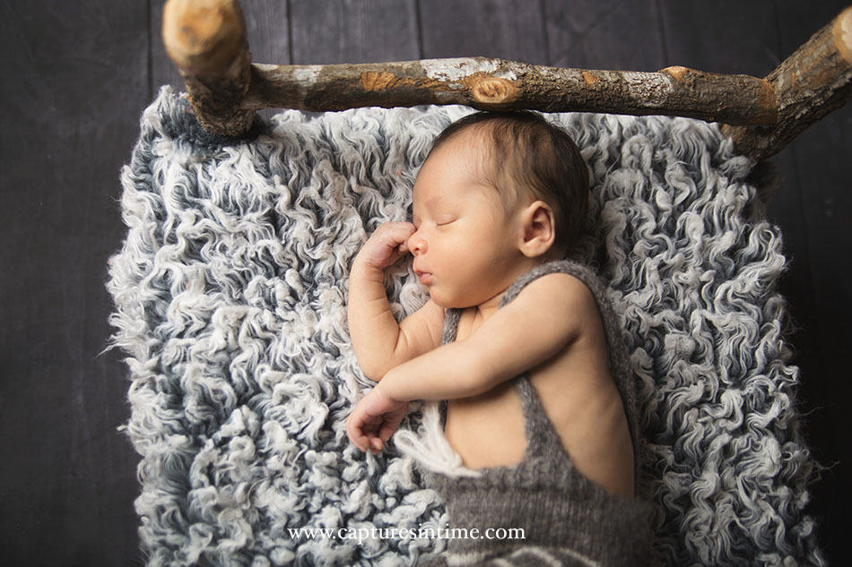 KC Newborn Photographer baby sleeping on grey rug in a twig bed with a romper on