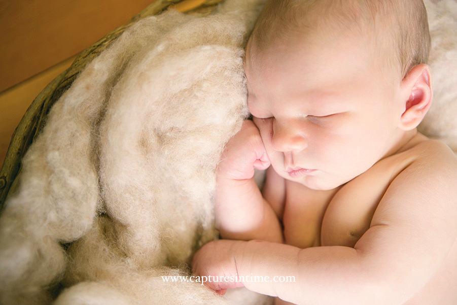 Kansas City Golf Newborn Photography sweet little baby with his fist on face