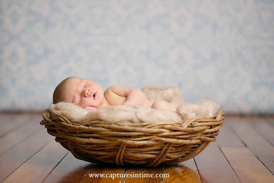 Kansas City Golf Newborn Photography newborn laying in brown fluffy texture in front of blue damask backdrop