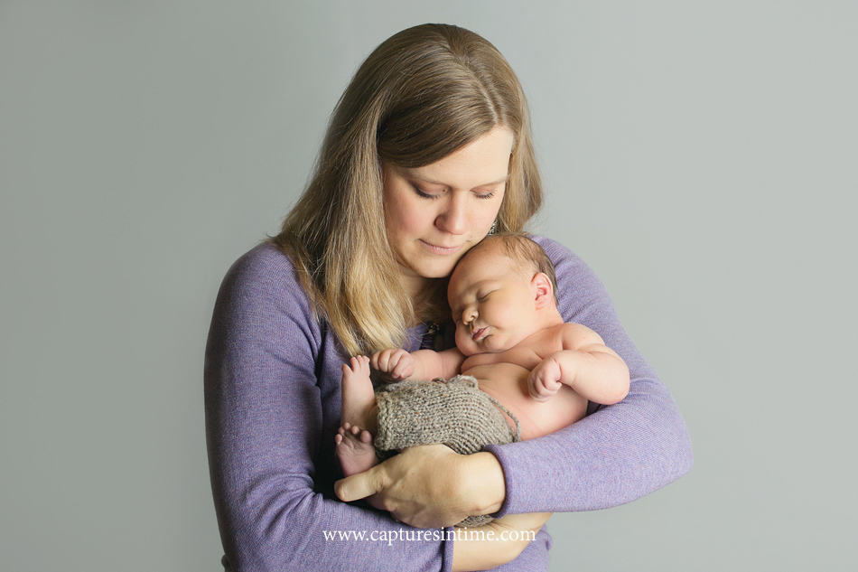 mom in lavender sweater holding new baby boy