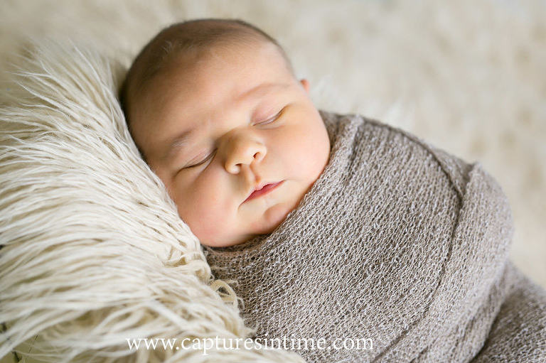newborn baby boy swaddled laying on side on cream fur rug