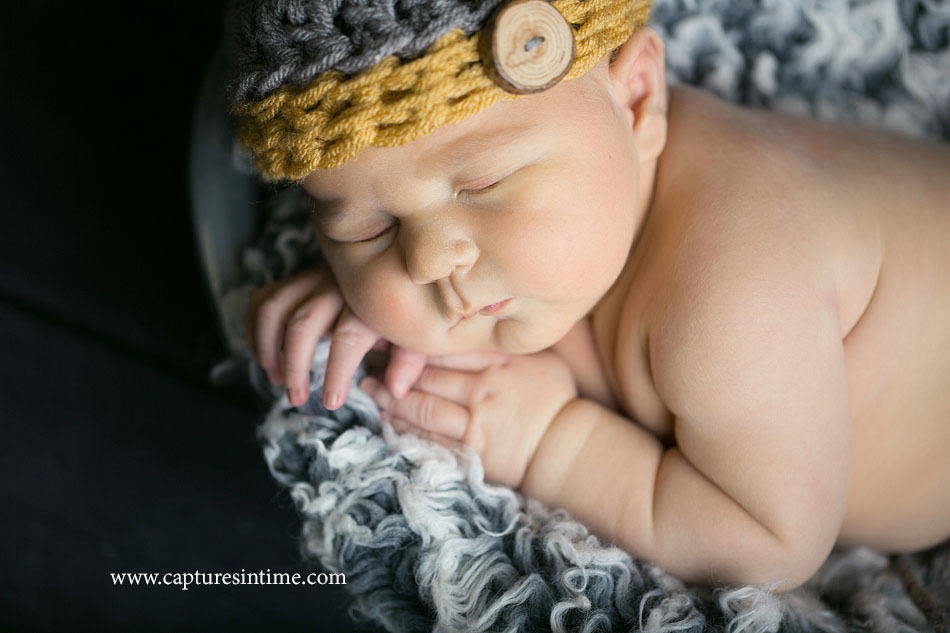newborn baby boy with rolls wearing yellow and gray hat