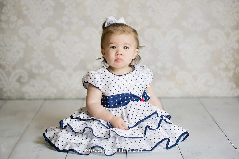 baby photography lees summit toddler in polka dot dress in front of grey damask backdrop on white floor