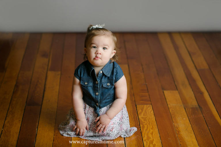 baby photography lees summit girl making funny face in denim and floral outfit on vintage floor